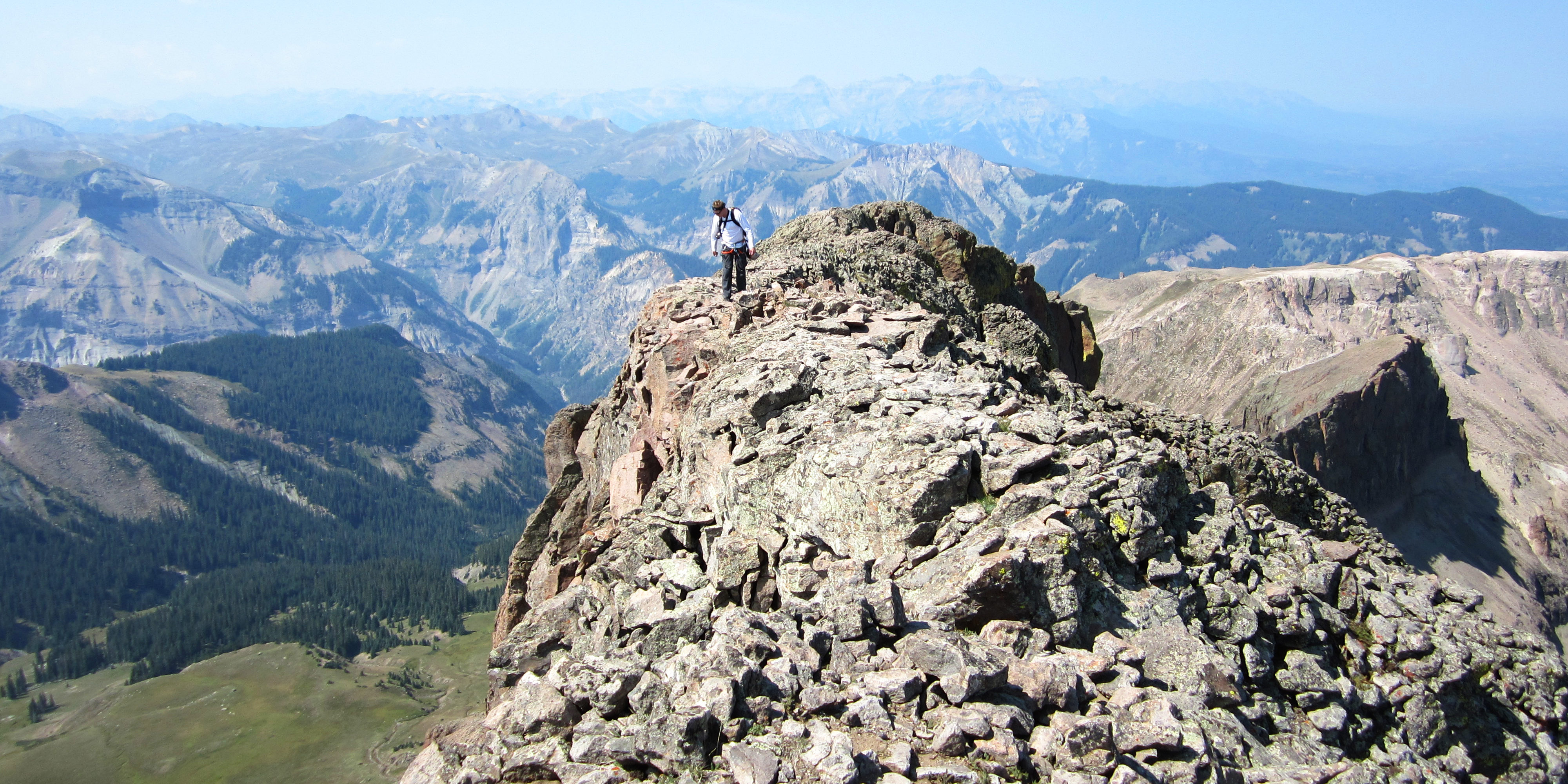 Tommy admiring the drop of the south side of Coxcomb Peak's summit ridge.